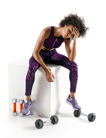 Headache. Sporty african girl is tired after intense workout on white background. Health concept.