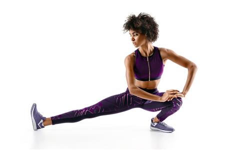Atletenmeisje die haar hamstrings uitrekken. Foto van jong Afrikaans meisje die het uitoefenen op witte achtergrond doen. Sport Stockfoto
