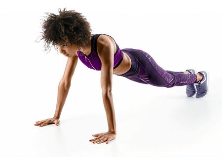 プッシュアップしている強い女の子。白い背景に孤立した運動をしているスポーティなアフリカの女の子の写真。強さとモチベーション