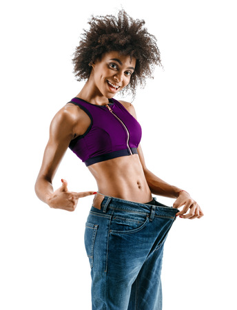 Sporty girl pulling her big jeans and showing weight loss. Photo of african girl on white background. Strength and motivation Stock Photo