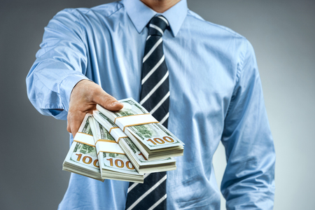 Man in blue shirt holding cash of one hundred dollars. Close up. Business concept