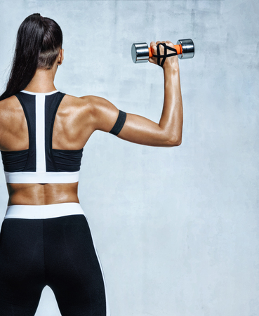Strong woman working out with dumbbells, flexing her arm. Photo of sporty woman in sportswear on grey background. Rear view