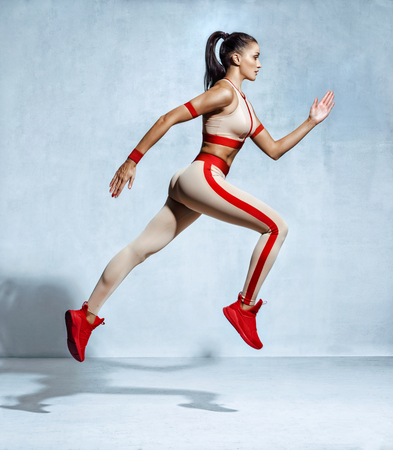 Sporty woman runner in fashionable sportswear on grey background. Dynamic movement. Side view Stock Photo