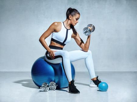 Mulher forte que elabora com os dumbbells que sentam-se na esfera ginástica. Foto da mulher latin desportiva no sportswear no fundo cinzento. Esportes