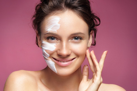 Young woman with moisturizing facial mask on pink background. Photo of pretty woman receives the spa treatments. Beauty & Skin care concept