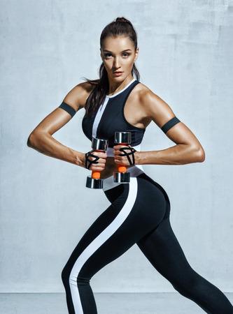 Junge lateinische Frau, die Übung mit Dummköpfen tut. Foto der sportlichen Frau im Training, das oben Muskelhände auf grauem Hintergrund pumpt. Kraft und Motivation Standard-Bild
