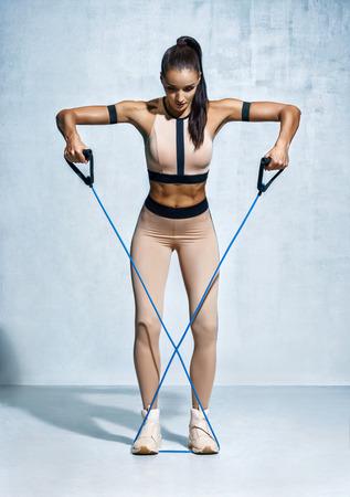 Fitness meisje voert oefeningen met weerstandsband uit. Foto van geschiktheids modeltraining op grijze achtergrond. Kracht en motivatie