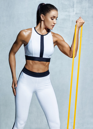 Athletic girl performs exercises using resistance band. Photo of young latin girl pumping biceps on grey background. Strength and motivation