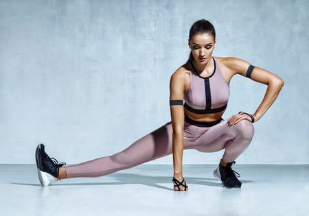 Athlete girl stretching her hamstrings. Photo of young latin girl doing exercising on grey background. Strength and motivation Stock Photo