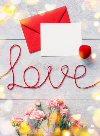 Red envelope with letter and rose flowers on wooden background. Valentines Day background Stok Fotoğraf