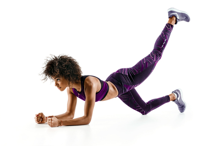 Beautiful young girl doing exercise on the floor. Photo of african girl in silhouette on white background. Fitness and healthy lifestyle concept