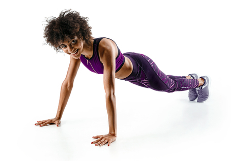 Smiling girl doing push ups. Photo of sporty african girl doing exercising isolated on white background. Strength and motivation