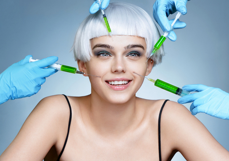 Pretty woman and beauticians hands with syringes making botox injection in her face. Rejuvenation therapy concept.