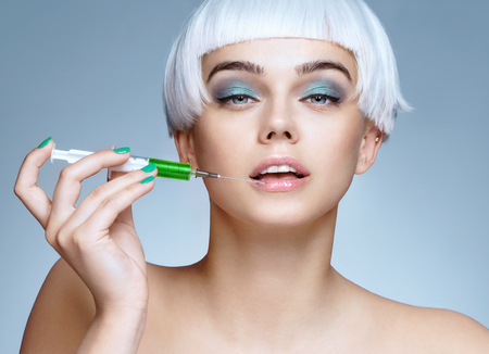 Beautiful woman face with syringe makes cosmetic injection in the lips. Clean Beauty concept