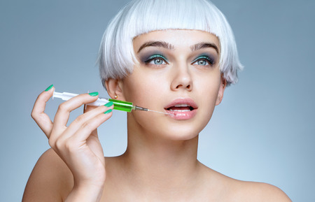 Beautiful woman with syringe making rejuvenate injection. Clean Beauty concept
