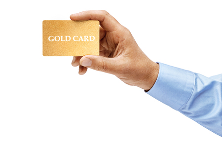 Mans hand in shirt holding gold credit card isolated on white background. High resolution product. Close up.