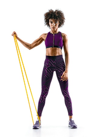 Strong girl using a resistance band in her exercise routine. Young african girl performs fitness exercises on white background. Strength and motivation