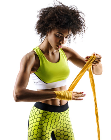 Boxer strapping up hands. Photo of sporty african girl preparing her gloves for a fight in silhouette on white background. Fitness and healthy lifestyle concept