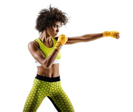 Boxer Frau macht direkten Schlag . Foto der sportlichen afrikanischen Frau während Boxen auf weißem Hintergrund . Dynamische Bewegung . Seitenansicht