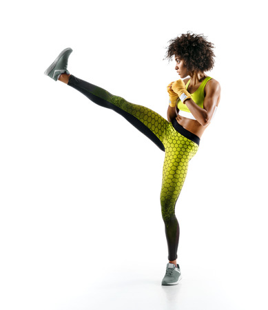 Girl practicing tae-bo exercises, kicking forward with legs. Photo of sporty african girl on white background
