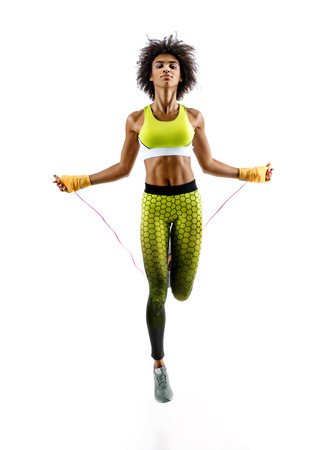 Young girl with skipping rope on white background. Best cardio workout
