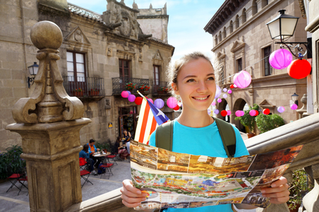 Travel in Spain. Tourist holding travel map. Smiling girl walking along spanish streets in Valencia 写真素材