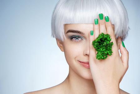 Beautiful smiling girl with parsley in her hand. Photo of fashion blonde girl on blue background. Close up. Healthy lifestyle concept 写真素材