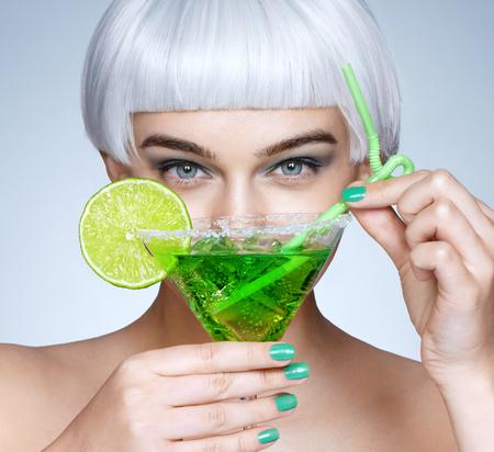 彼女の顔の前に緑のカクテルを持つグラマラスな女の子。青い背景にファッションブロンドの女の子の写真。クローズアップ 写真素材