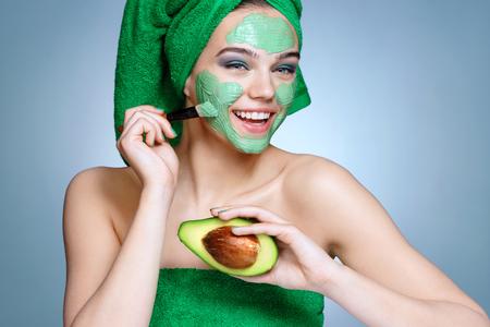 Niña feliz que recibe la máscara facial cosmética. Retrato de niña sonriente con una toalla sobre su cabeza sobre fondo azul. Prepararse Foto de archivo