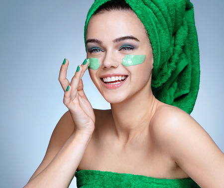 Laughing girl applying moisturizing cream on her face. Photo of young girl with flawless skin in green towels. Skin care and beauty concept Stockfoto