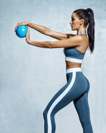 Sporty girl with ball for gymnastics. Photo of strong young girl in training muscles hands on grey background. Strength and motivation