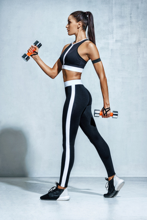 Perfect sporty woman working out with dumbbells. Photo of woman in black sportswear on grey background. Side view. Full length
