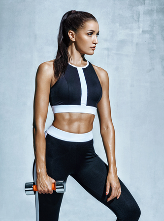 Sporty woman with dumbbell. Photo of muscular woman in black sportswear on grey background. Strength and motivation.