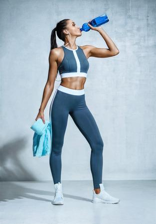 Deportiva chica agua potable después del ejercicio. Foto de chica latina fitness sobre fondo gris. Estilo de vida saludable