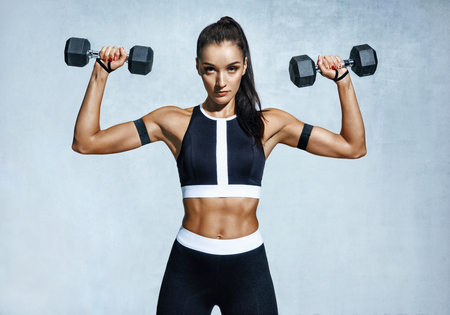 Beautiful young woman doing exercises with dumbbells. Photo athletic woman with perfect body on grey background. Strength and motivation
