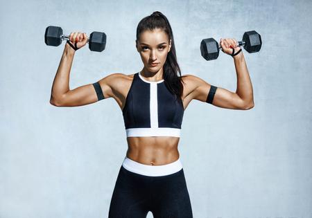 Schöne junge Frau, die Übungen mit Dummköpfen tut. Athletische Frau des Fotos mit perfektem Körper auf grauem Hintergrund. Kraft und Motivation Standard-Bild
