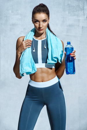 Attractive woman with muscular body holding bottle of refreshing water. Resting time. Health concept 스톡 콘텐츠