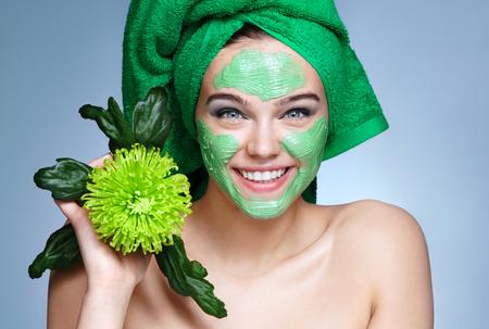 化粧品の顔のマスクを受け取る笑顔の女の子。青い背景に緑のタオルと緑の菊の花のかわいい女の子の写真。自分自身をグルーミング