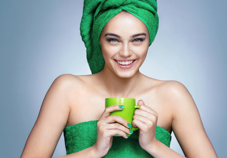 Good morning! Attractive girl in green towels with cup of tea on blue background. Stock Photo