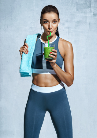 Healthy lifestyle. Photo of latin fitness girl with towel and glass of detox cocktail on grey background. Standard-Bild
