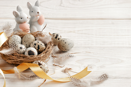 Easter background with Easter eggs and spring flowers. Top view with copy space. Stock Photo