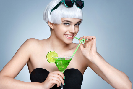 Cheerful fashion girl with glass of cocktail on blue background. Party. Summer time
