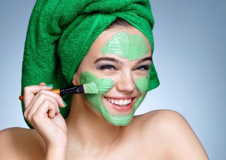 Hermosa jovencita que recibe la máscara facial cosmética. Retrato de niña sonriente con una toalla verde sobre su cabeza sobre fondo azul. Prepararse