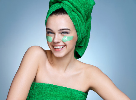 Smiling girl in green towels with moisturizing cream on her face. Photo of young girl with flawless skin on blue background. Skin care and beauty