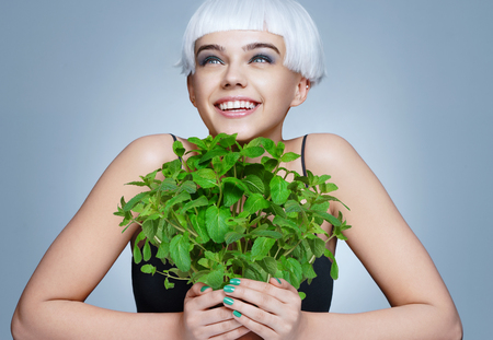 Cheerful girl holding organic mint bush on blue background. Healthy & Happy Stok Fotoğraf