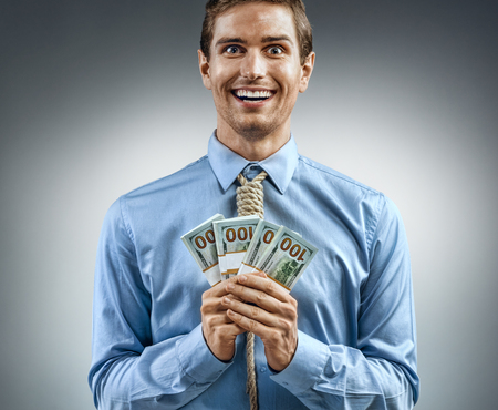 Happy man holding cash money. Photo of smiling man in blue shirt and tie in the form of loop on his neck on grey background