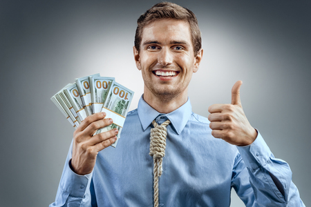 Man holding cash money and showing thumb up. Photo of smiling man in blue shirt and tie in the form of loop on his neck on grey background Stock Photo