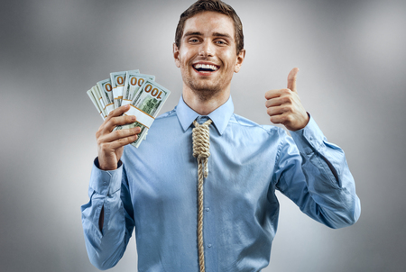 Man holding cash money and showing thumb up. Photo of smiling man in blue shirt and tie in the form of loop on his neck on grey background Reklamní fotografie