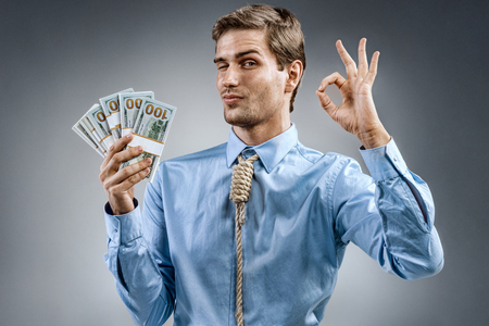 Man holding cash money and showing okay sign. Photo of smiling man in blue shirt and tie in the form of loop on his neck on grey background