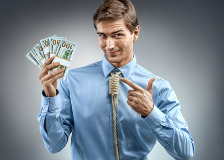 Man holding cash money and pointing a finger at them. Photo of smiling man in blue shirt and tie in the form of loop on his neck on grey background
